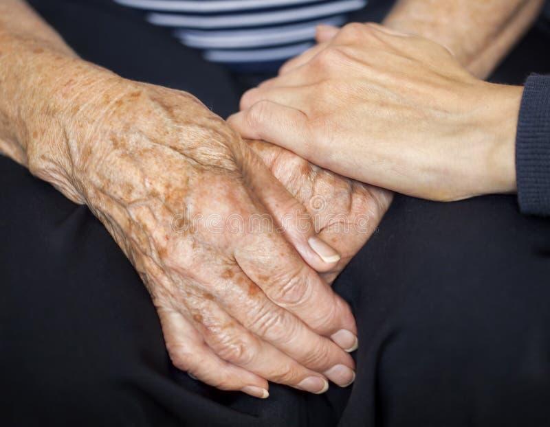 Junge Hand, die alte Hände tröstet stockfotografie