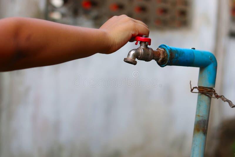 Junge Handdrehend weg von einem alten rostigen Wasserhahn für speicherndes wasser- Sicherungswasserkonzept - ökologisches und K stockfotos
