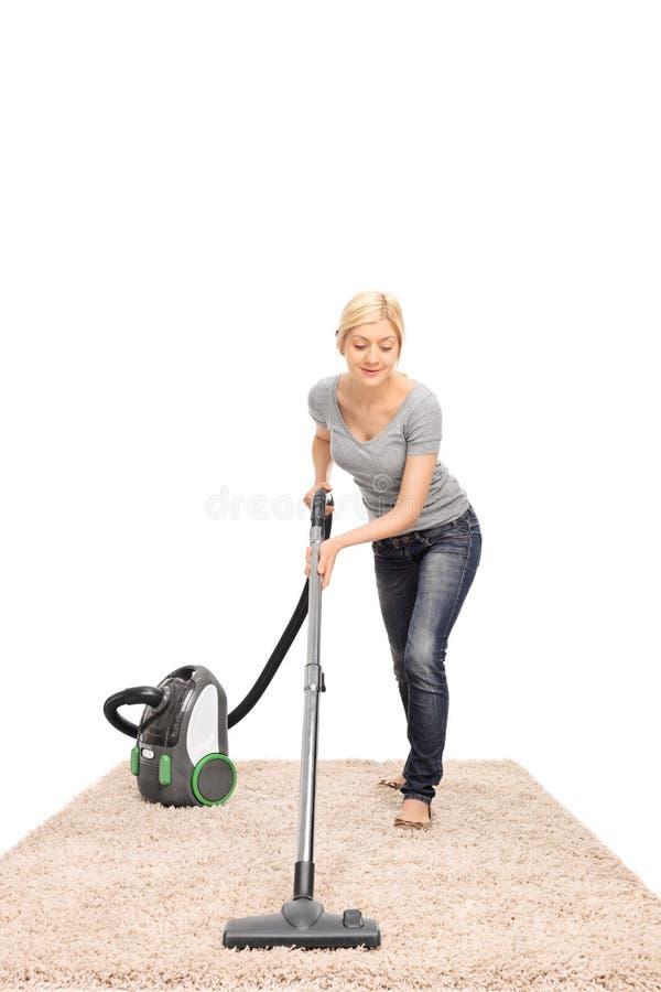 Junge Hausfrau, die einen Teppich Staub saugt stockbilder