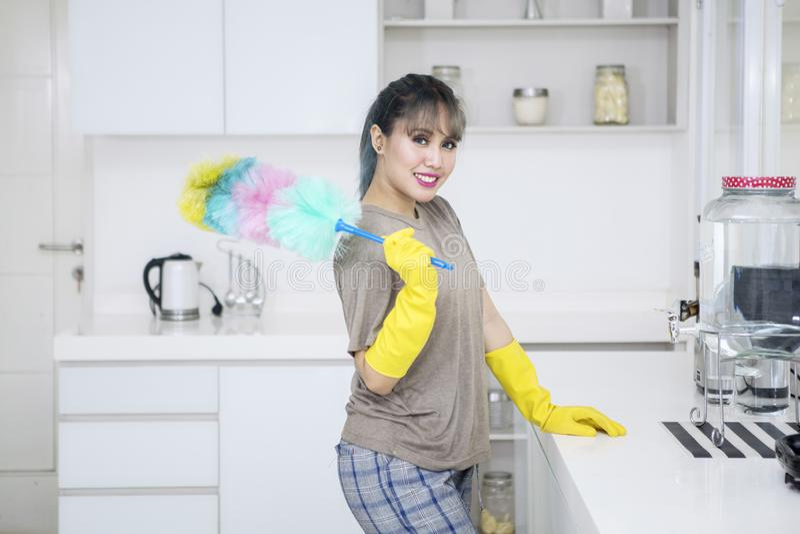 Junge Hausfrau hält eine Staubtuchbürste in der Küche stockbilder