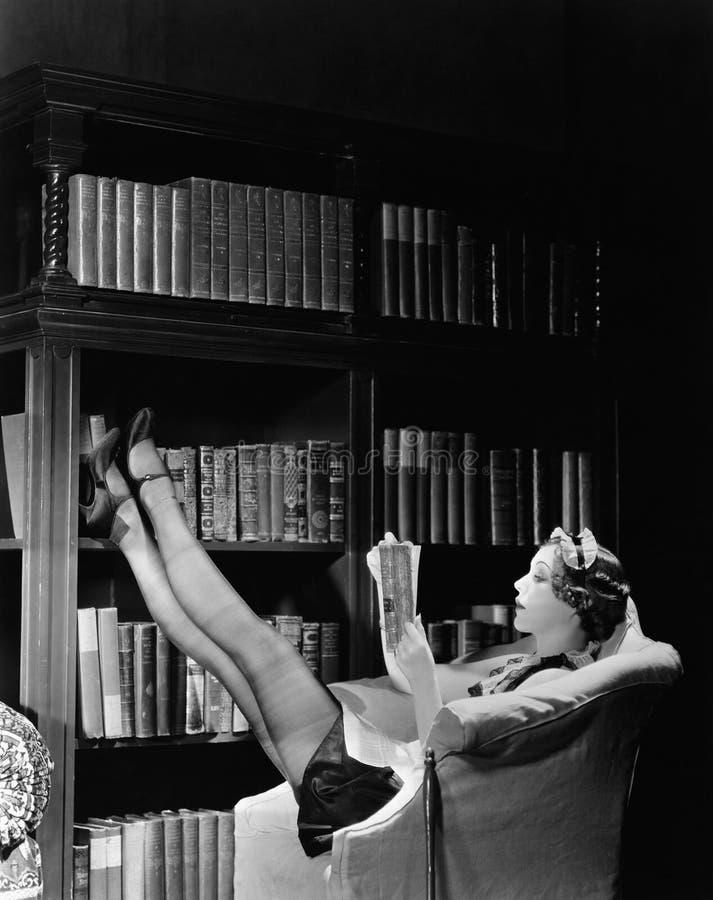 Junge Haushälterin, die ein Buch beim Stützen in einen Bibliothekslehnsessel liest (alle dargestellten Personen sind nicht länger stockfotos