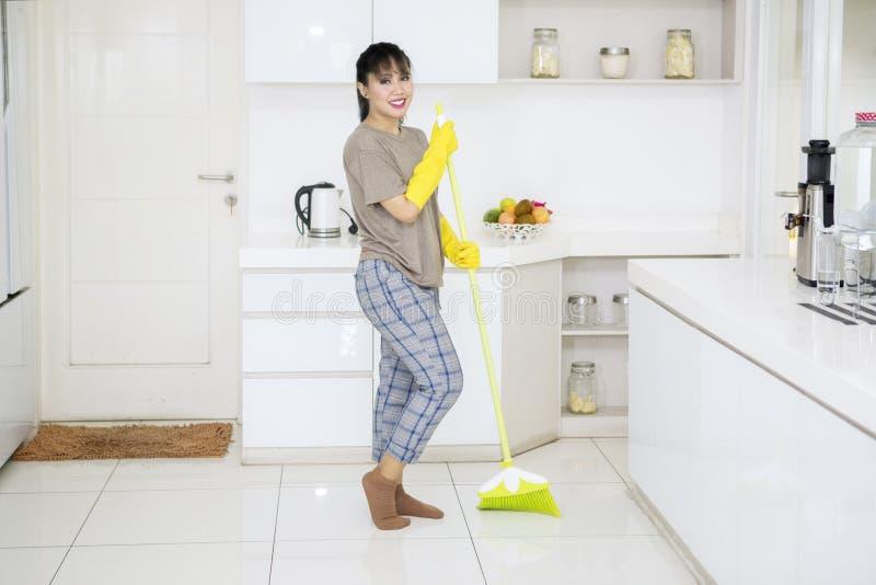 Junge Haushälterinreinigungsböden mit einem Besen lizenzfreies stockbild