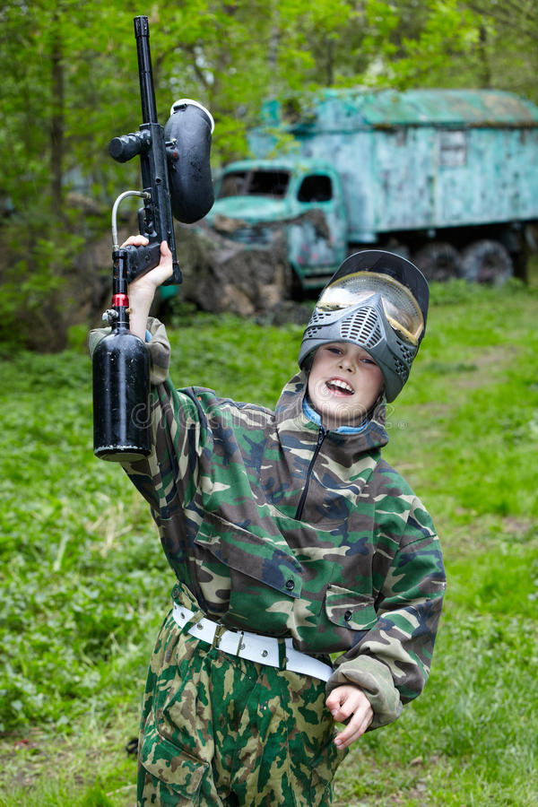 Junge hebt Hand mit Paintballgewehr an lizenzfreie stockbilder