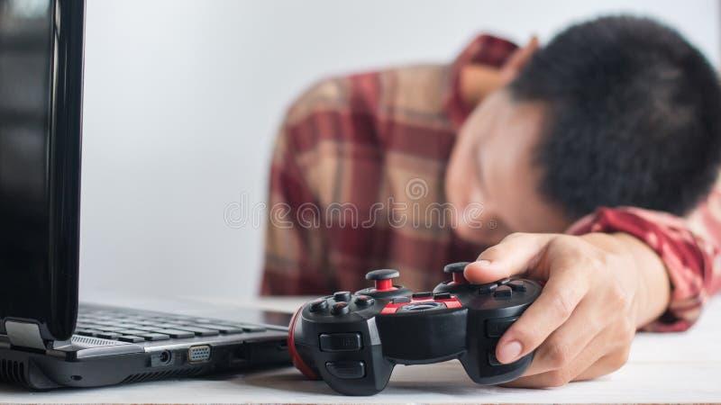 Junge Herrenbekleidungs-rotes Scott-Musterhemdschlafen Handholding Steuerknüppelgamepad und -laptop lizenzfreie stockfotos