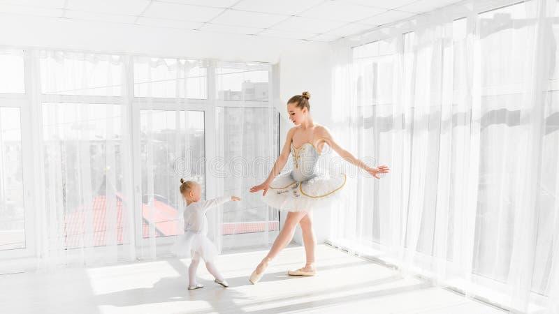 Junge herrliche Ballerina mit ihrem kleinen Tochtertanzen im Studio lizenzfreies stockfoto