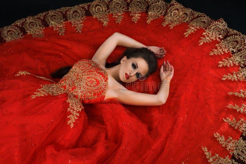 Junge herrliche träumerische Frau, die im roten Kleid liegt stockfotos