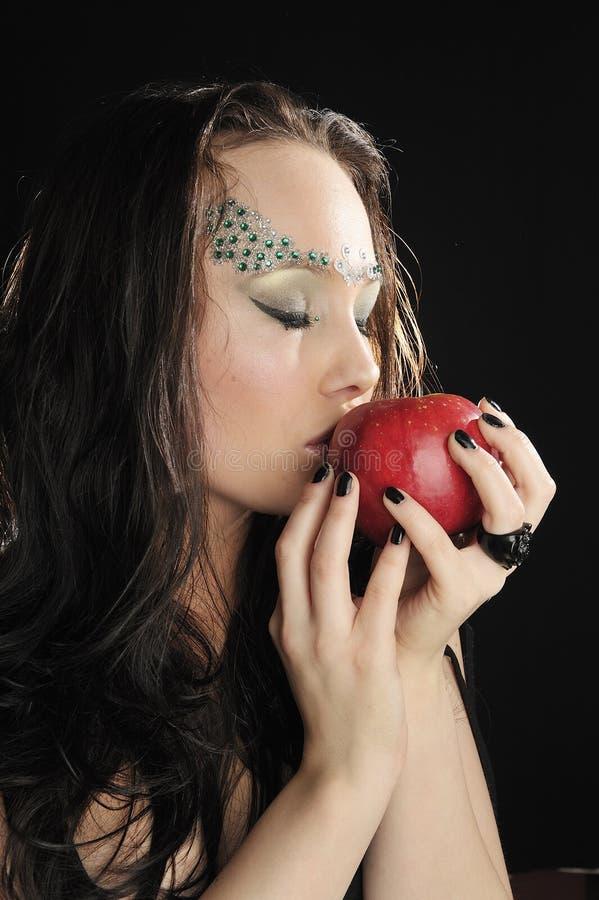 Junge Hexe, die einen roten Apfel küßt stockfoto