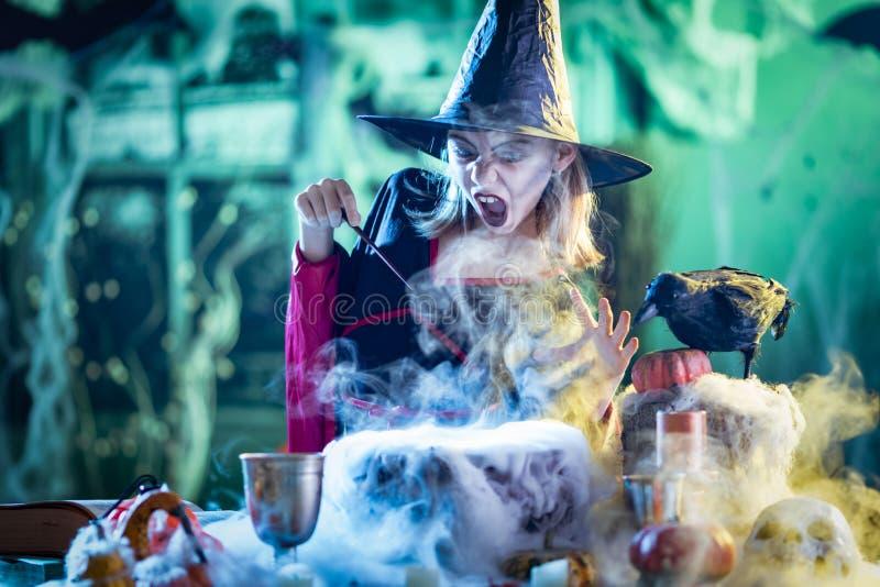 Junge Hexe kocht mit Magie stockfoto