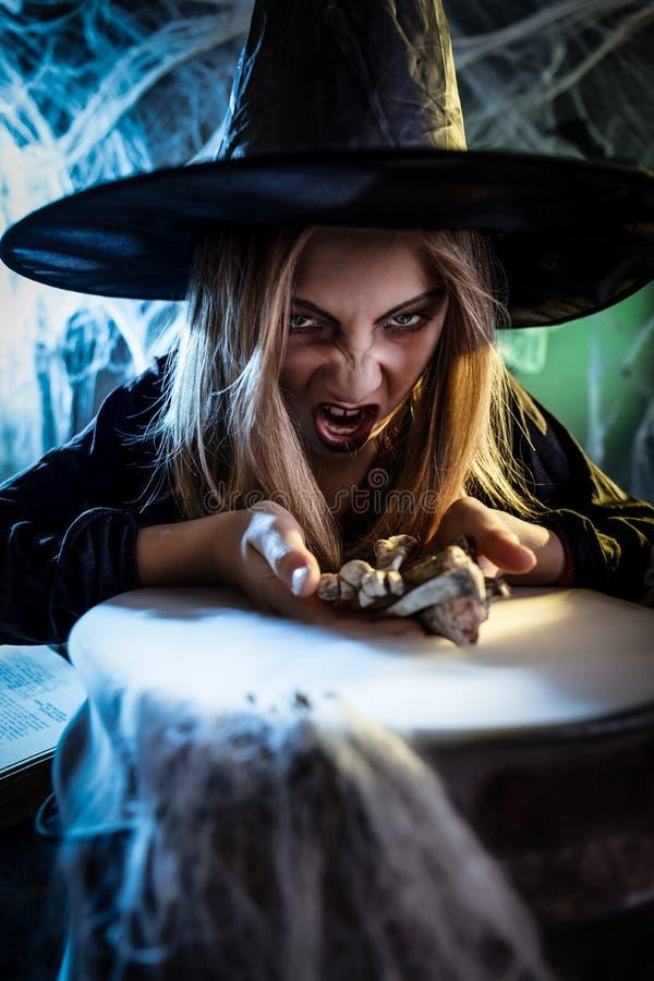 Junge Hexe kocht mit magischem Bouns stockfoto