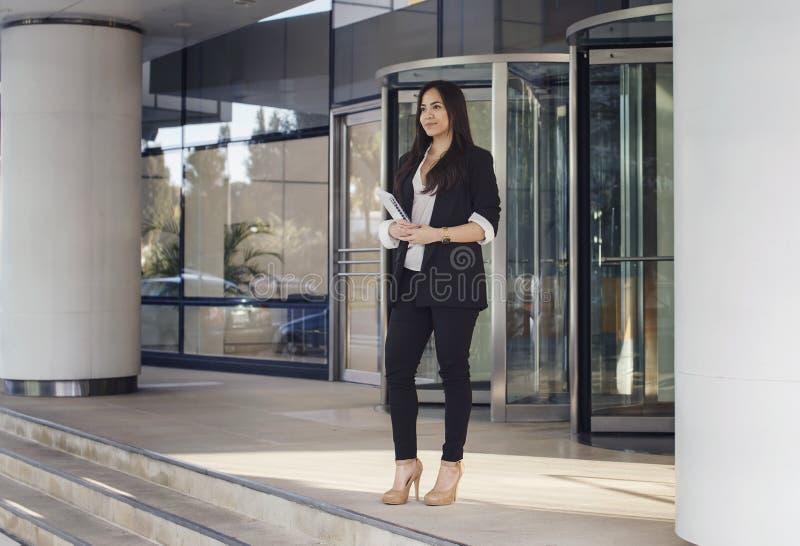 Junge hicpanic Geschäftsfrau, die im Büro stading ist lizenzfreie stockfotos