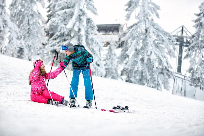 Junge hilft zum Mädchen, vom Schnee mit Skis aufzustehen stockbild