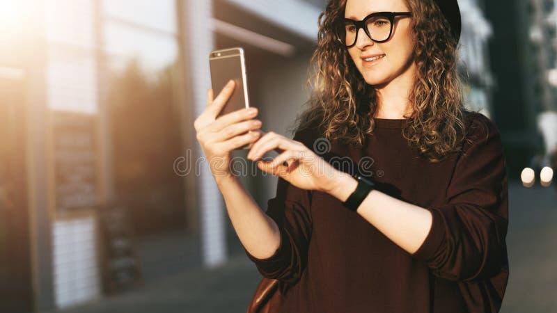 Junge Hippie-Frau in den modischen Gläsern und in den Hutwegen auf Stadtstraße und Gebrauch Smartphone Social Media, Lebensstil lizenzfreie stockbilder