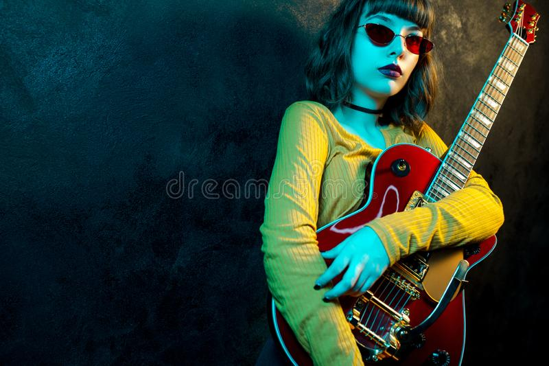 Junge Hippie-Frau der Mode mit dem gelockten Haar mit roter Gitarre in den Neonlichtern Felsenmusiker spielt elektrische Gitarre stockfotografie