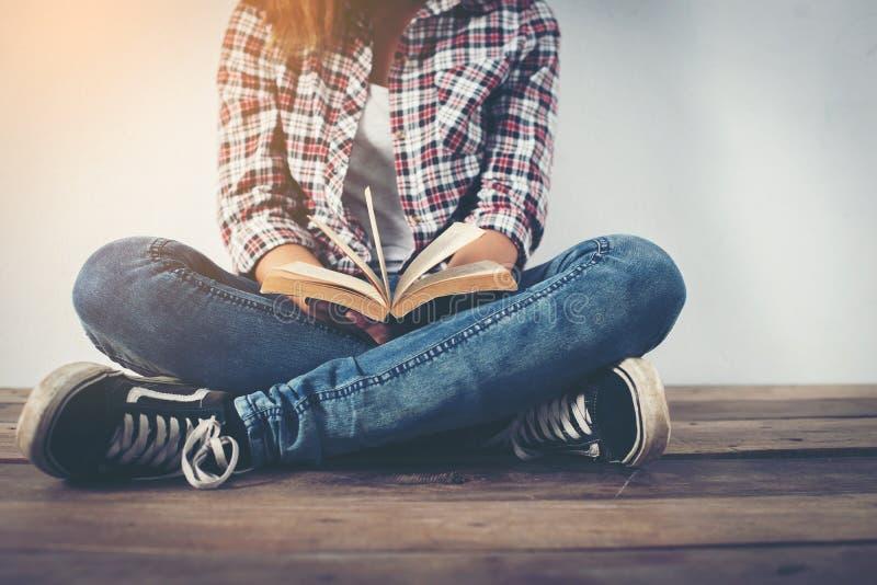 Junge Hippie-Frau, die das offene Buch sitzt auf Bretterboden hält lizenzfreie stockbilder