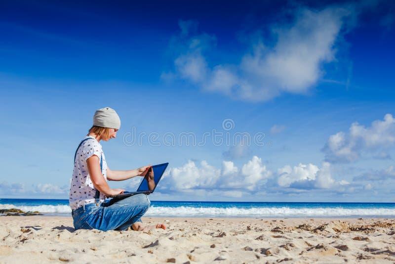 Junge Hippie-Frau, die an Laptop am Strand arbeitet lizenzfreie stockbilder