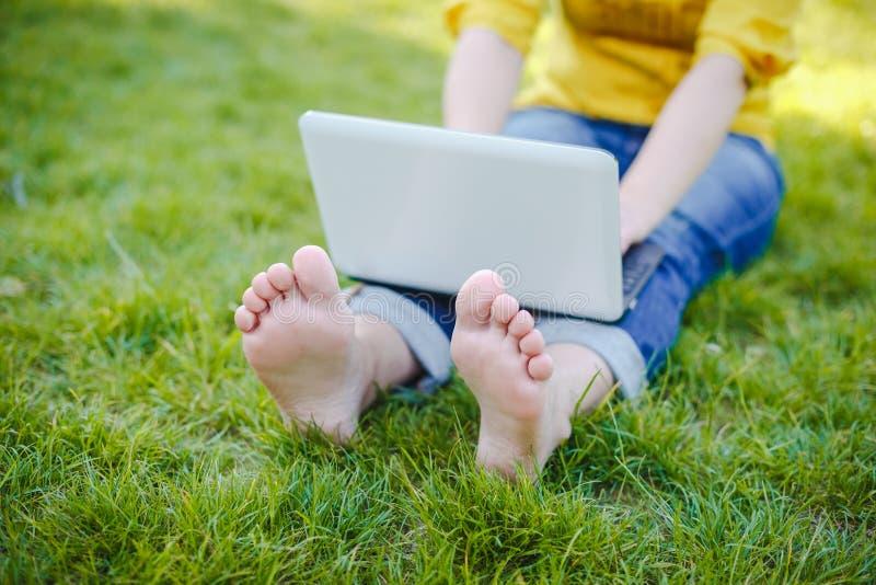 Junge Hippie-Mädchenfüße mit Laptop in einem Park lizenzfreie stockbilder