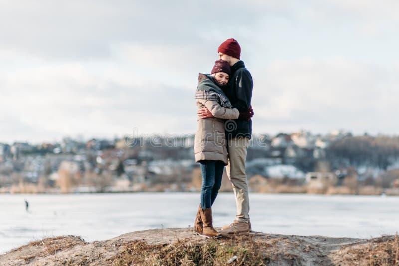 Junge Hippie-Paare, die im Winterpark sich umarmen lizenzfreies stockbild