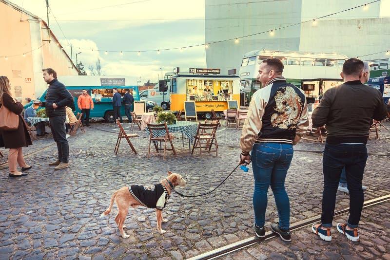 Junge Hippies, die um Stadtgebiet der Stadt mit schnellem Gastronomiebereich und Restaurants im Freien gehen stockbilder