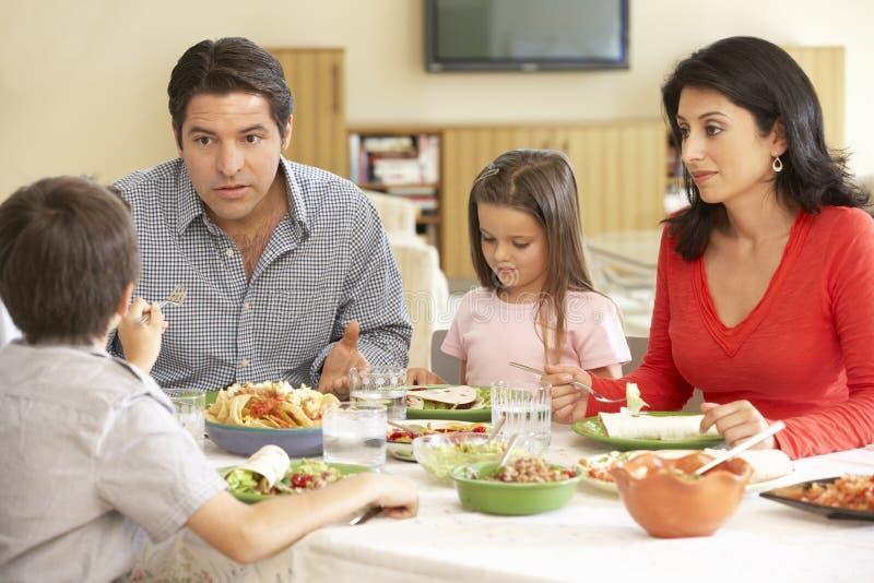 Junge hispanische Familie, die zu Hause Mahlzeit genießt stockfotografie