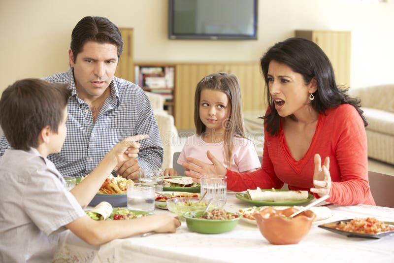 Junge hispanische Familie, die zu Hause Mahlzeit genießt lizenzfreies stockfoto