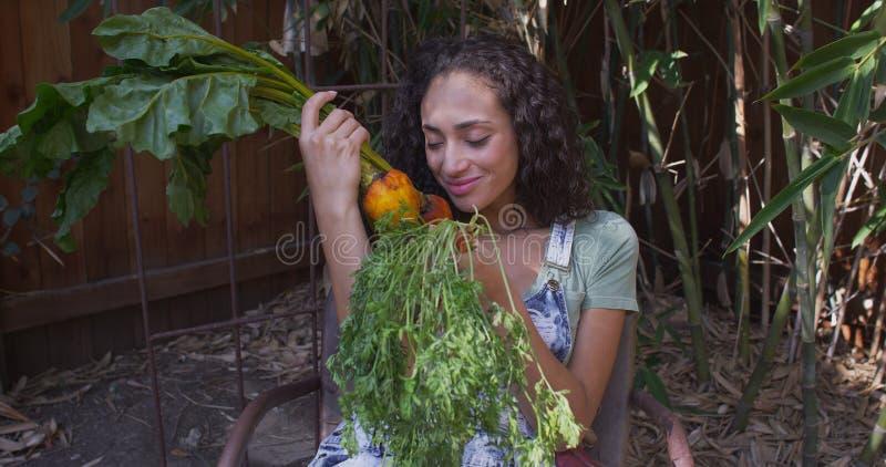 Junge hispanische Frau, die Gemüse riecht und betrachtet lizenzfreies stockfoto