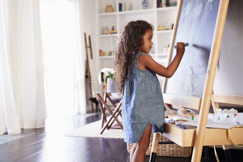 Junge hispanische Mädchenzeichnung mit Kreiden an einer Tafel im Wohnzimmer zu Hause, Seitenansicht lizenzfreie stockbilder