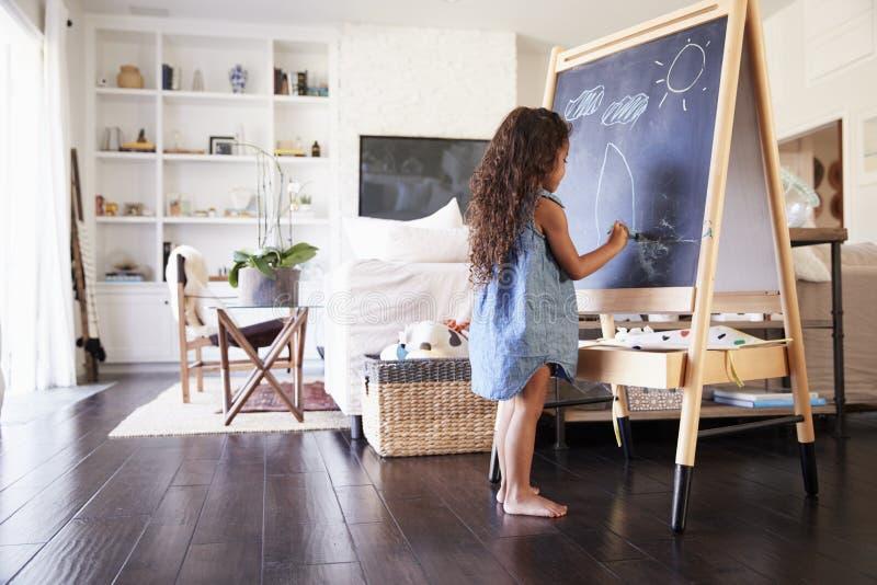 Junge hispanische Mädchenzeichnung mit Kreiden an einer Tafel im Wohnzimmer zu Hause, in voller Länge lizenzfreie stockfotos