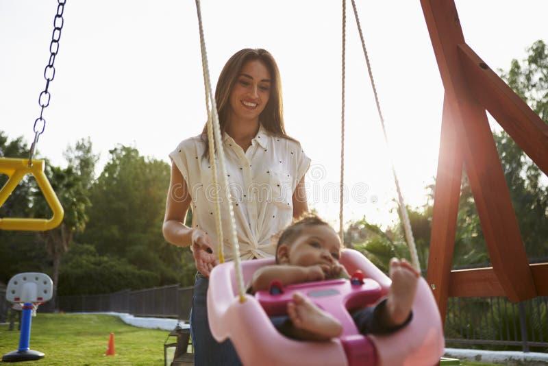 Junge hispanische Mutter, die ihr Baby auf einem Schwingen an einem Spielplatz im Park, Abschluss hochdrückt stockfotografie