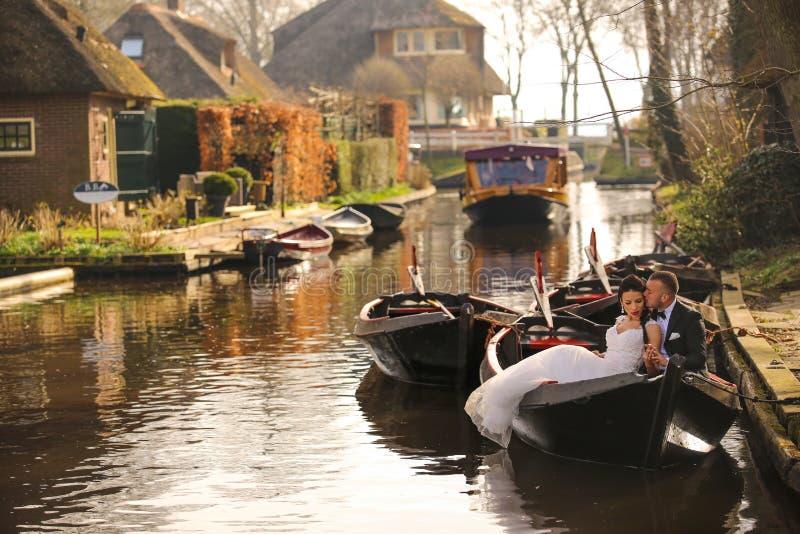 Junge Hochzeitspaare, die auf dem Boot aufwerfen lizenzfreies stockfoto