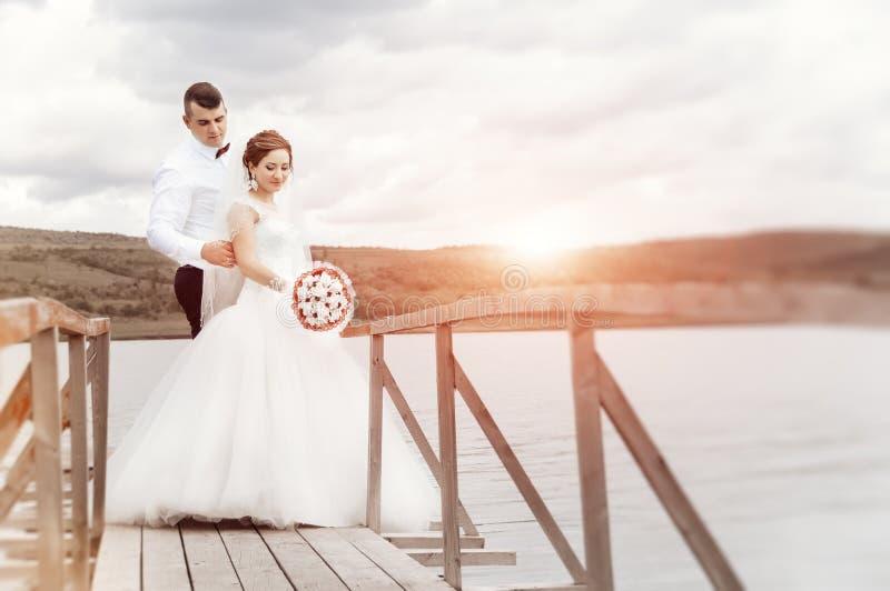 Junge Hochzeitspaare, die draußen romantische Momente nahe bei t genießen stockfotografie