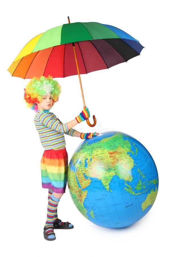 Junge im Clownkleid mit Regenschirm und großer Kugel lizenzfreies stockbild