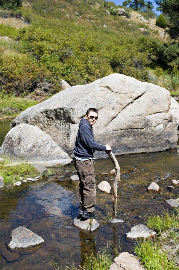Junge im Fluss durch einen Fluss-Stein stockfotos