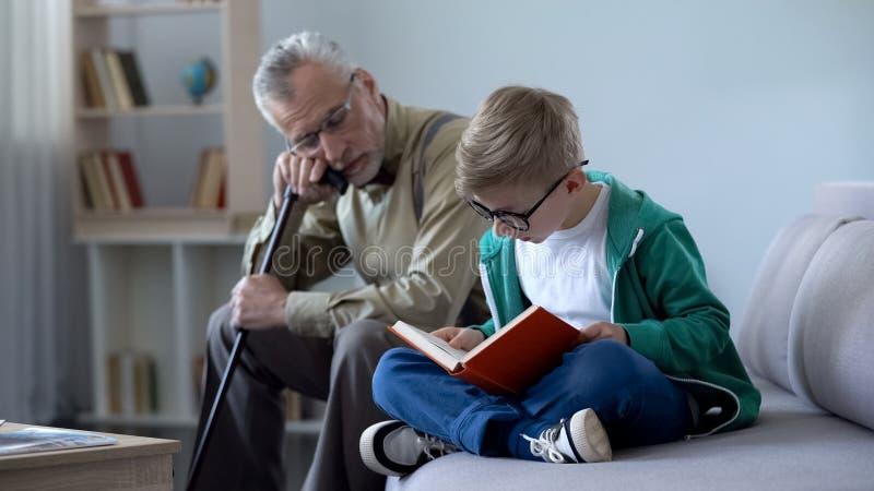 Junge im Glaslesebuch für Großvater, alter Mann, der auf angenehmes Sofa einschläft lizenzfreies stockbild