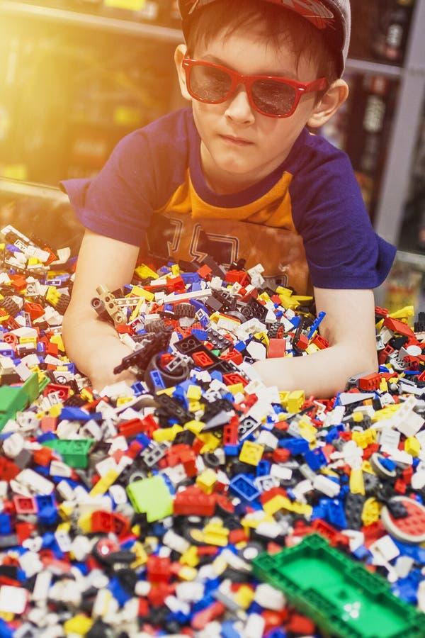 Junge im Glasspiel mit vielen Spielwaren lizenzfreie stockfotos