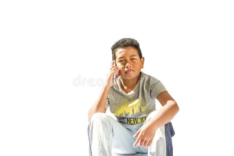 Junge im grundlegenden schulpflichtigen Alter nennend mit Handy lizenzfreie stockfotografie
