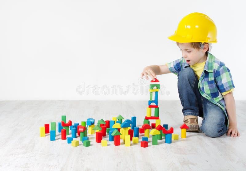 Junge im harten Hut, der mit Blöcken spielt stockfotografie