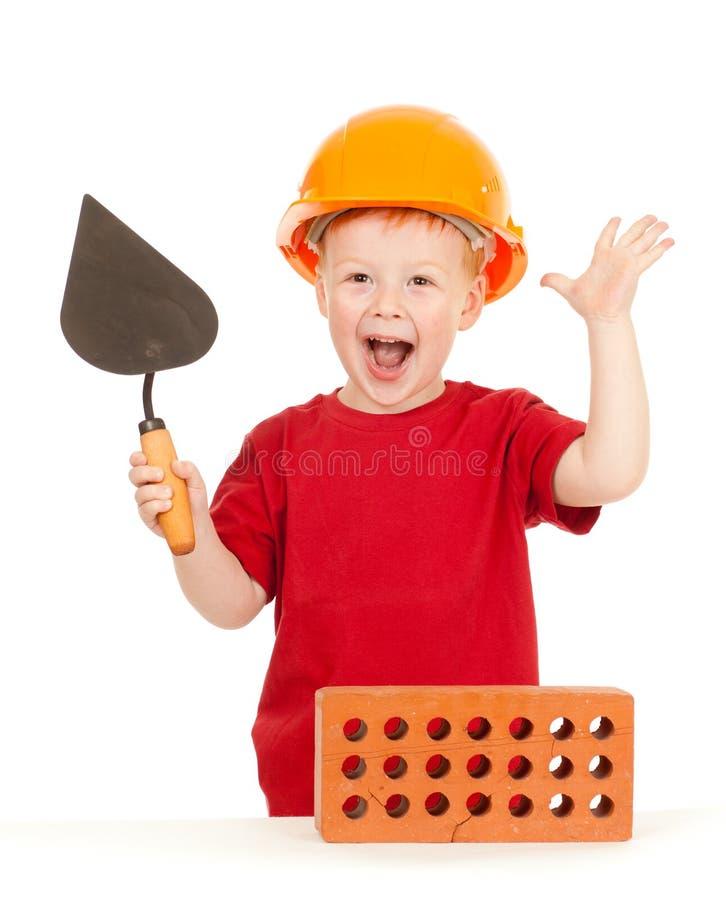 Junge im harten Hut mit Trowel und Ziegelstein getrennt stockfotografie