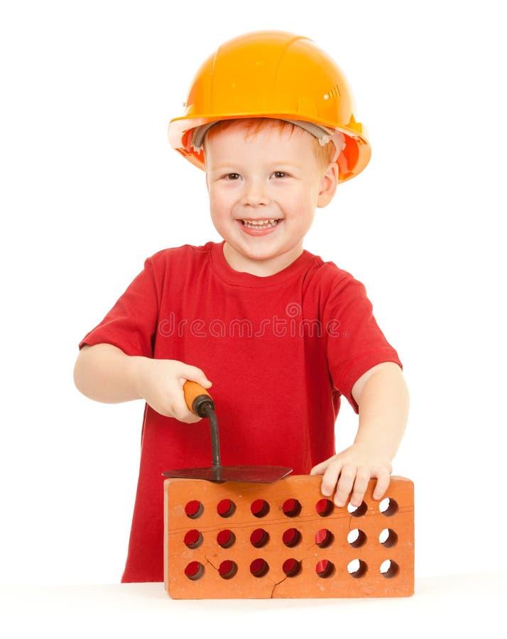 Junge im harten Hut mit Trowel und Ziegelstein getrennt lizenzfreies stockbild