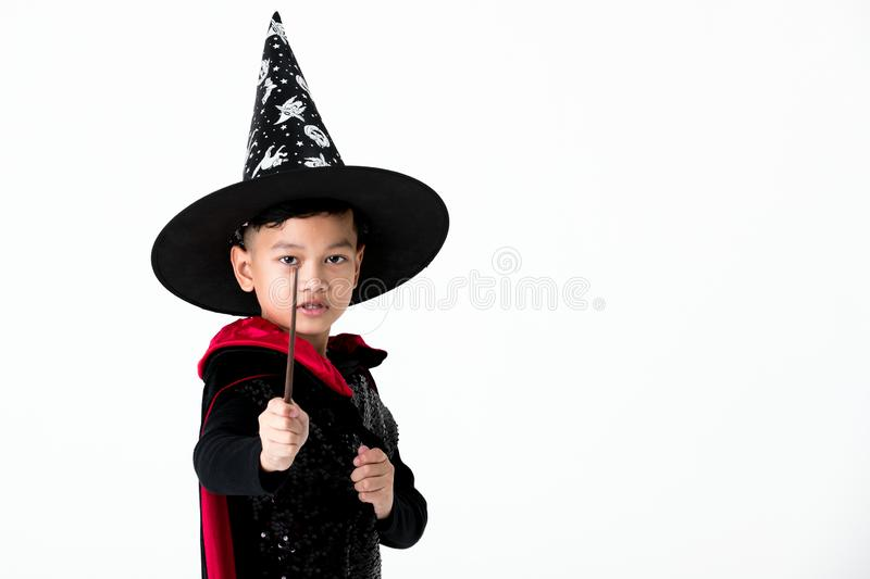 Junge im Hexenkostümkleid, das magischen Stab und Punkt t hält lizenzfreie stockbilder