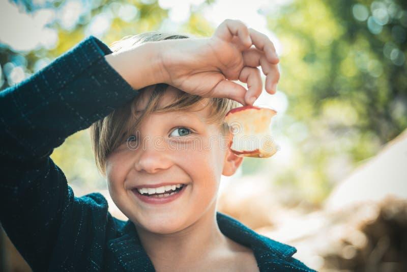 Junge im Hut, der Apfel und Lügen auf dem Heu hält Netter kleines Kinderjunge, der Goldblatt auf Bauernhofdorfhintergrund hält stockfoto