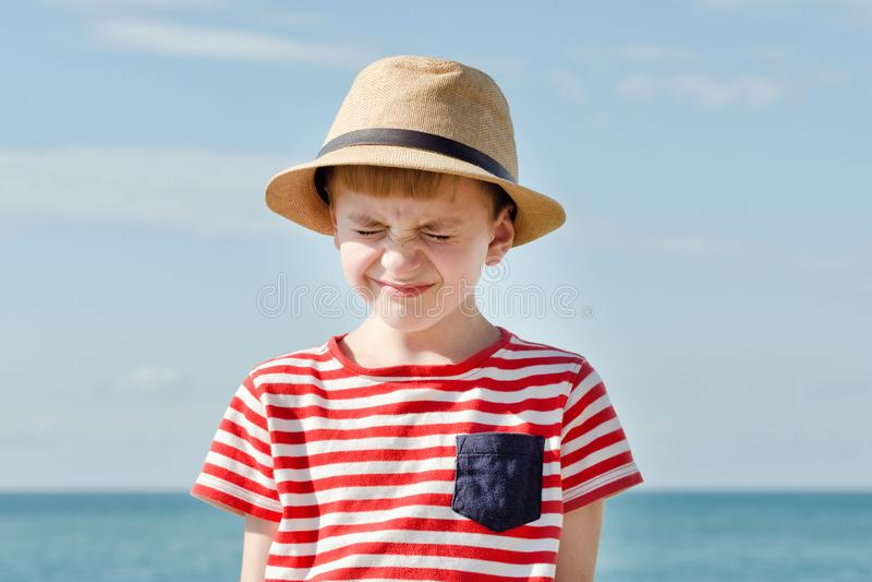 Junge im Hut, der von der Sonne schielt Meer auf Hintergrund lizenzfreies stockfoto