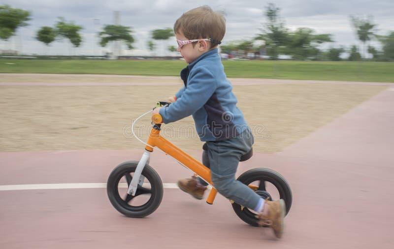 Junge im Matrosen, der schnell ein orange Balancenfahrrad oder ein Laufbi reitet lizenzfreies stockbild