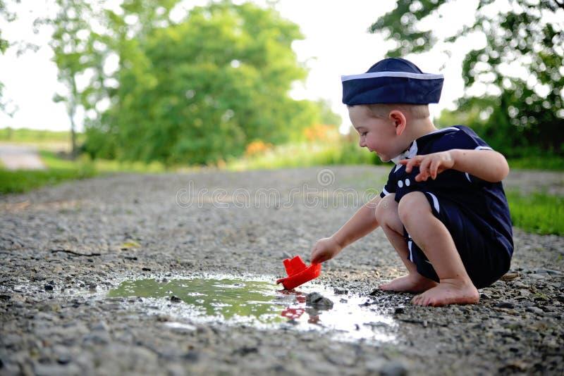 Junge im Matrosenanzug, der rotes Boot in einer Pfütze schwimmt stockfoto