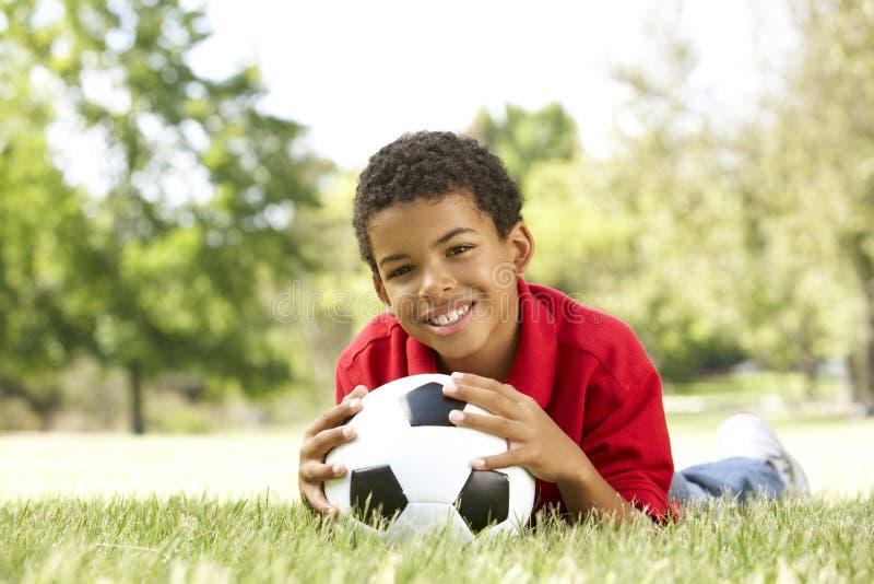 Junge im Park mit Fußball-Kugel stockfotos