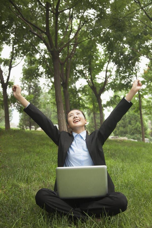Junge Im Park Sitzende Und, Unter Verwendung Ihres Laptops Ausdehnende Geschäftsfrau Stockfotografie