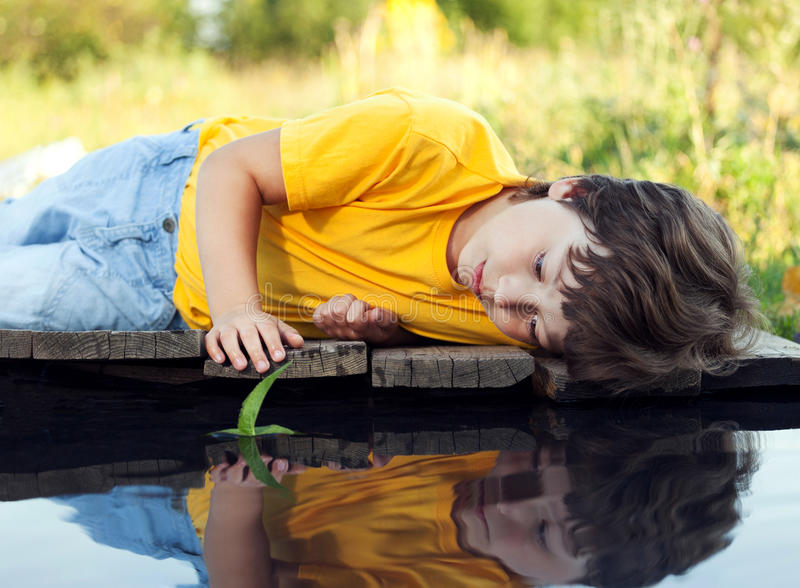 Junge im Parkspiel mit Boot im Fluss lizenzfreie stockbilder