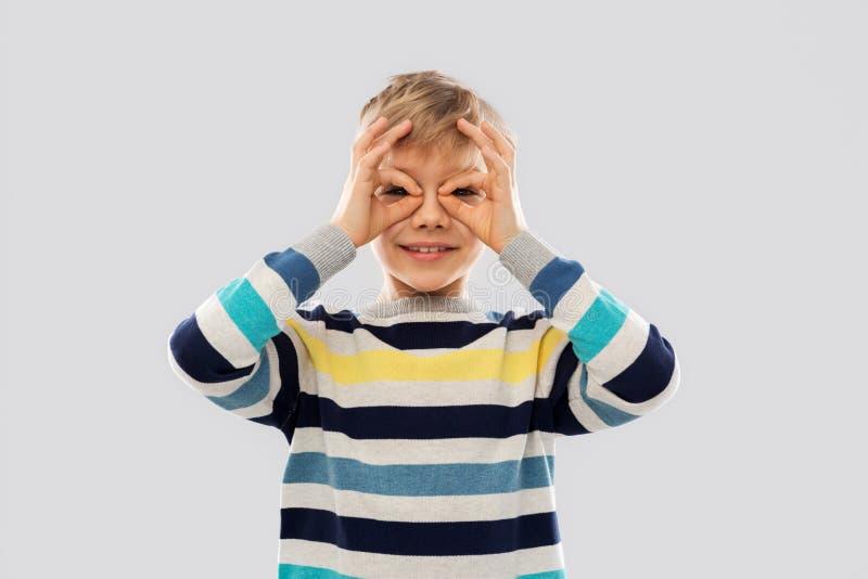 Junge im Pullover, der durch Fingergläser schaut stockfotos