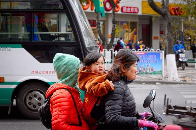 Junge im Roller mit seiner Schwester und seiner Mutter lizenzfreie stockfotos