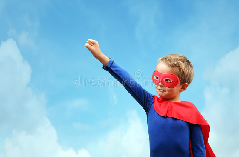 Junge im rotem Superheldkap und -maske stockbild