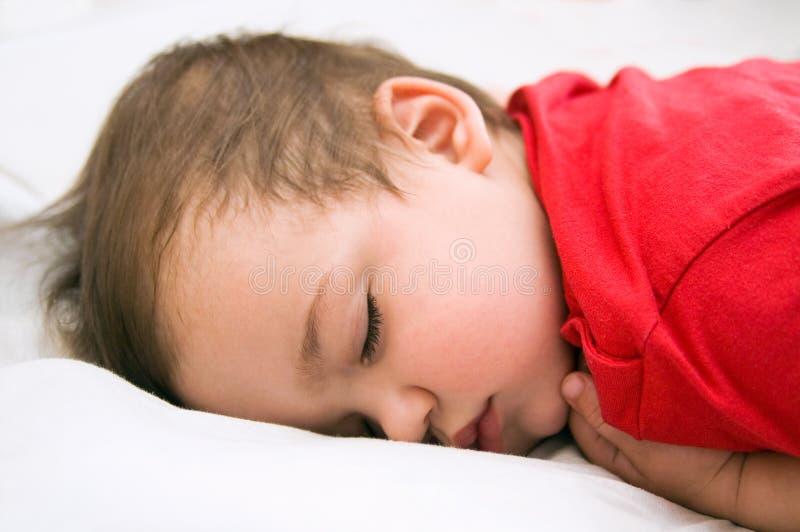 Junge im roten Kleid schlafend auf Bett lizenzfreie stockbilder